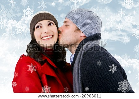 A young couple in love, surrounded by snowflakes - stock photo