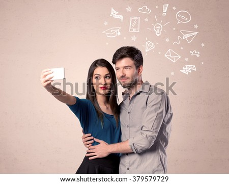 A young couple in love taking selfie with a mobile phone in the handsome guy's hand and drawn media communication icons above them, confused ideas concept - stock photo