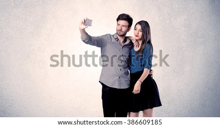 A young couple in love taking selfie with a mobile phone in the handsome guy's hand in front of an empty clear grey wall background concept - stock photo