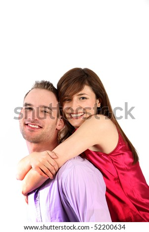 A young couple in love. The young man takes the young woman on his back. Both laugh in camera direction.