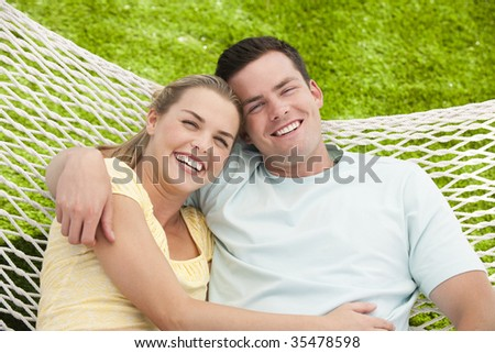 A young couple is cuddling in a hammock.  They are smiling at the camera.  Horizontally framed shot.