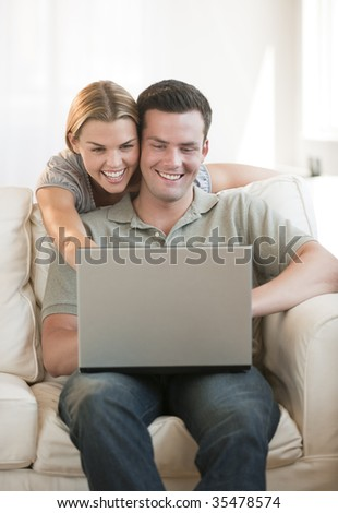 A young couple is looking at a laptop together in their living room.  Vertically framed shot.