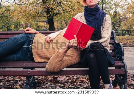 A young couple is reading and relaxing on a park bench in autumn - stock photo