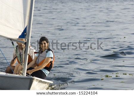 A young couple is sailing on a lake together.  They are looking at the camera.  Horizontally framed shot. - stock photo