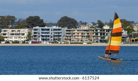 A young couple is sailing towards condominiums in Mission Bay, San Diego, California. A perfect metaphor for sailing to first home ownership through the sea of life. - stock photo