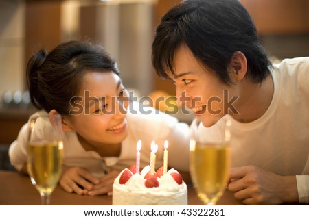 A young couple is smiling with birthday cake and champagne