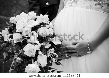 A young couple just married carrying their first child. - stock photo