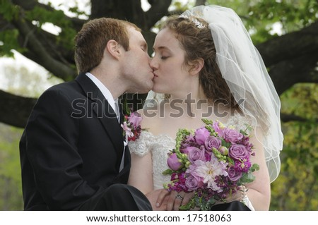 A young couple kisses in front of a large tree on their wedding day