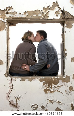 A young couple kissing in a window frame of an old building, blank background - stock photo