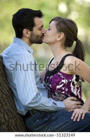 A young couple kissing in the park. - stock photo