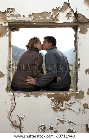 a Young couple kissing inside a window frame of an old building - stock photo