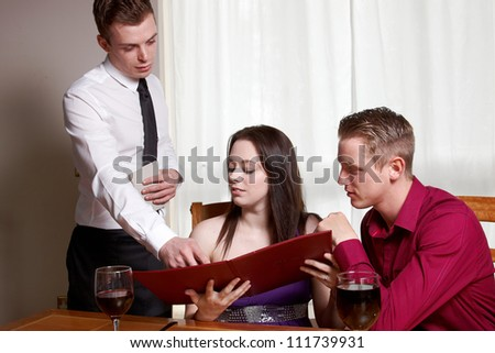 A young couple looking at a menu  in a restaurant - stock photo