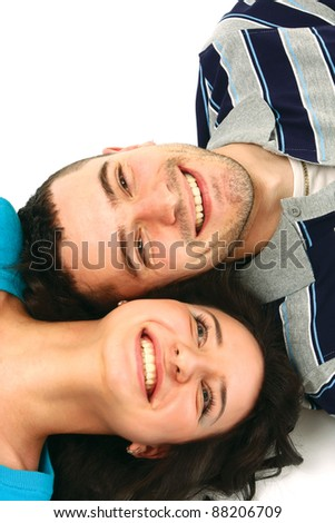 A young couple lying, looking at each other, isolated on white background