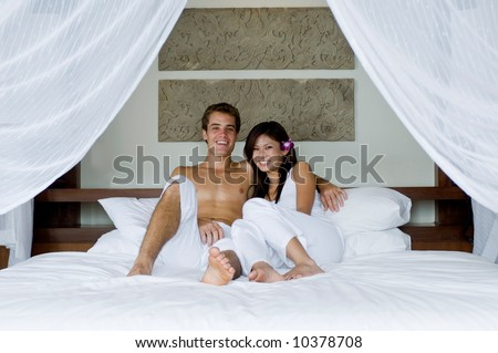 A young couple lying on bed in hotel room - stock photo