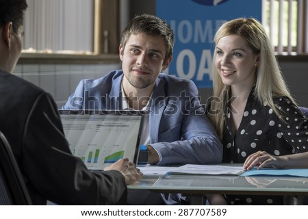 A young couple meeting with a banker for a home loan - stock photo