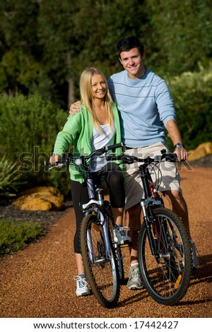 A young couple on bicycles in the countryside
