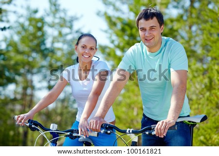 A young couple on bicycles looking at camera and smiling - stock photo