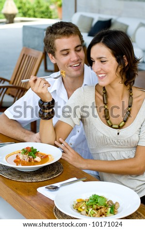 A young couple on vacation eating lunch at a relaxed outdoor restaurant - stock photo