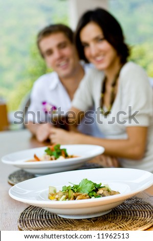 A young couple on vacation eating lunch at a relaxed outdoor restaurant (focus on food)