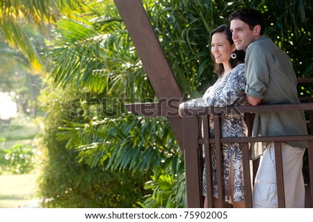 A young couple on vacation standing on the balcony - stock photo