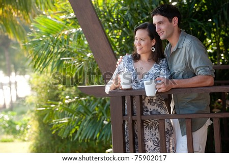 A young couple on vacation standing on the balcony holding mugs - stock photo
