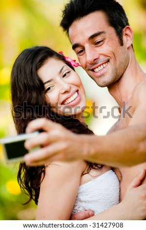 A young couple on vacation taking their photograph outside in tropical setting