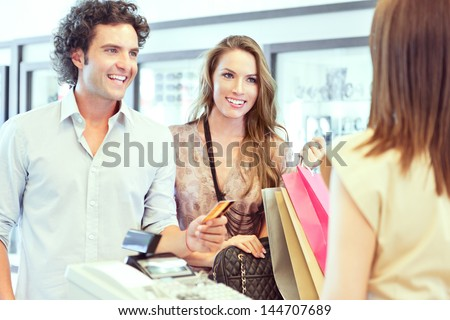 A young couple paying for the clothes they have just bought. - stock photo