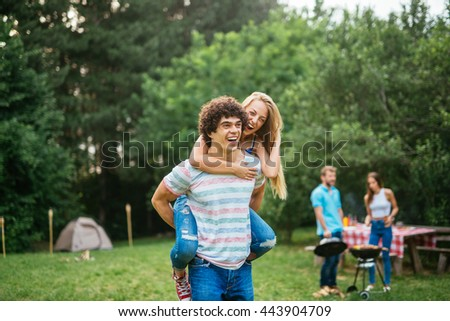A young couple piggybacking outdoors in the nature. - stock photo