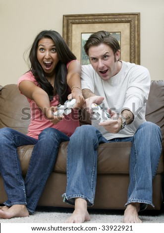 A young couple playing an intense video game - stock photo