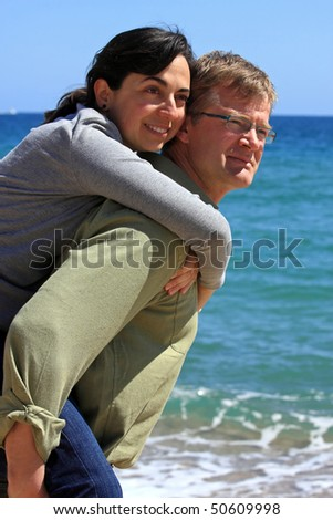 A young couple playing on the beach - stock photo