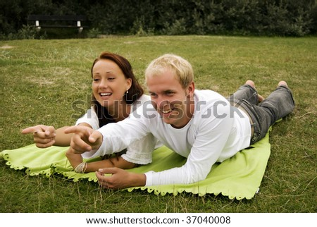 A young couple point to something in the distance during a romantic picnic. - stock photo