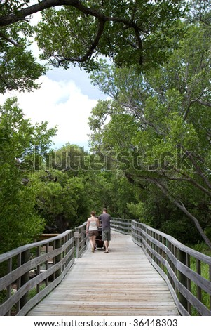 A young couple push a stroller along a raised wooden walkway in a preserve area of Anne's Beach in the Florida Keys. - stock photo