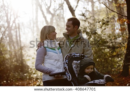 A young couple pushing a stroller in the park, smiling