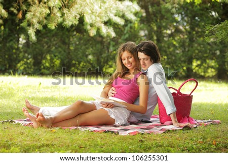 a young couple read a book together in the park - stock photo