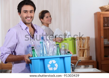 a young couple recycling plastic in their kitchen - stock photo