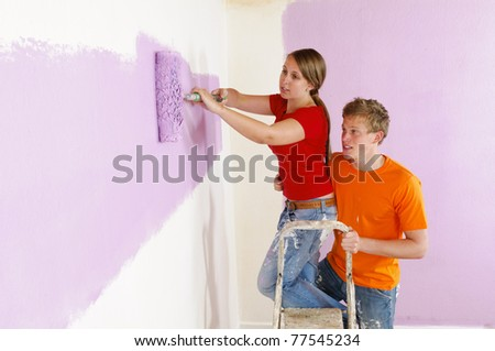A young couple renovated their first home together. They emphasize a lot of fun with the walls with paint roller and paint. - stock photo