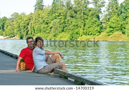 A young couple, sit on a lake dock, together. - horizontally framed