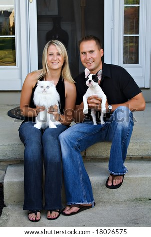 A young couple sits in front of their home with their pet cat and puppy.