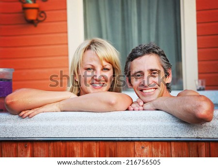 a young couple sitting in hot tub (focus is on the man) shallow DOF  - stock photo