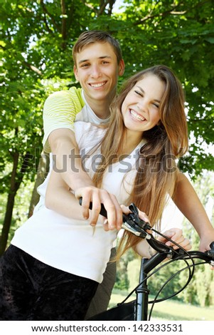 A young couple sitting on a bicycle - stock photo