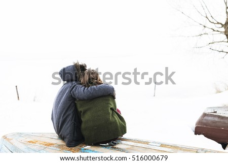 a young couple sitting on a boat near the frozen lake