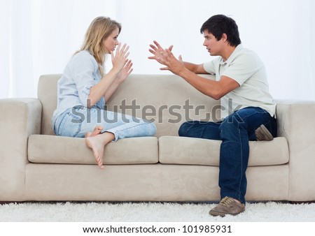A young couple sitting on a couch are having an argument - stock photo
