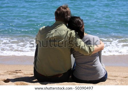 A young couple sitting on the beach - stock photo