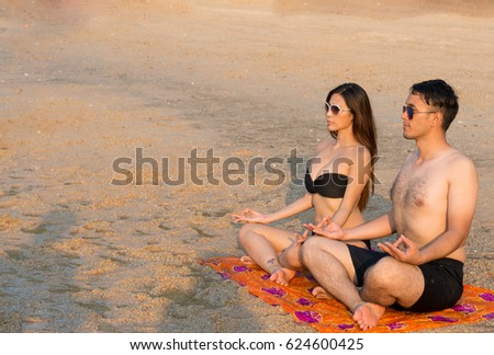 A young couple sitting on the beach in the lotus position ,Meditation yoga couple meditating at serene beach sunset,Girl and man relaxing in lotus pose in calm zen moment  during yoga holiday