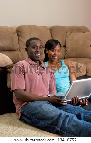 A young couple sitting on the floor by a sofa with a laptop.