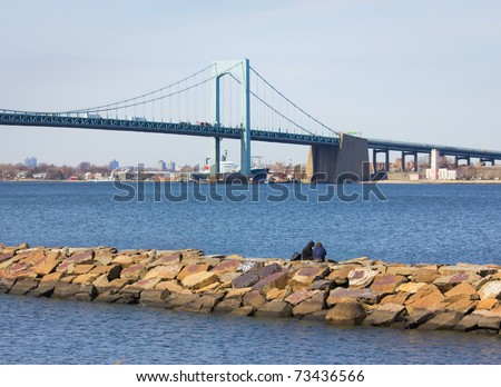 A young couple sitting on the rocky jetty by the long island sound, with New York City's Throgs Neck Bridge in the background - stock photo