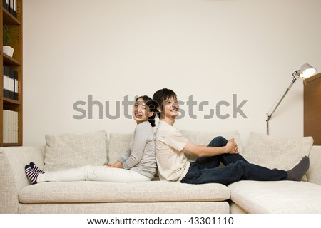 A young couple sitting on the sofa back-to-back - stock photo