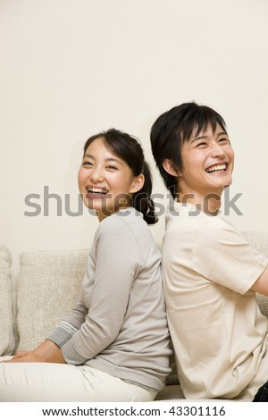 A young couple sitting on the sofa back-to-back and smiling