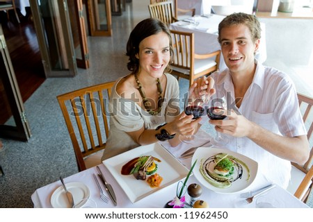 A young couple sitting together in a restaurant holding hands - stock photo