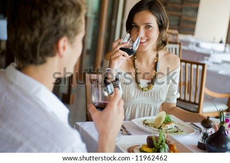 A young couple sitting together in a sophisticated restaurant - stock photo